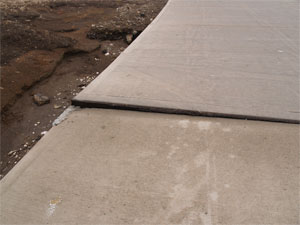 photo of a sinking concrete sidewalk with cracks in Claremore