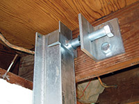Securing the i-beam system to the top of the floor joist in a foundation wall repair in Bixby.